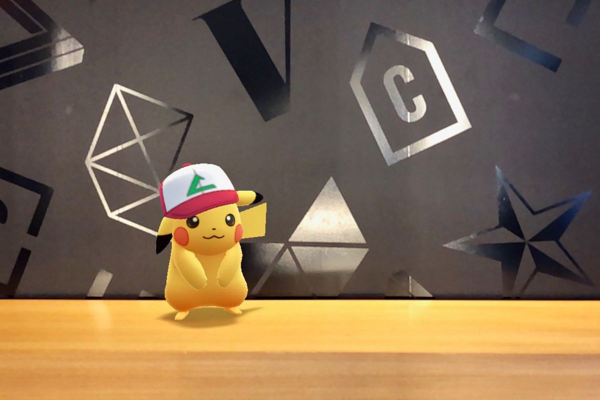 An Ash hat Pikachu from Pokémon Go poses adorably in front of a Vox Media wall