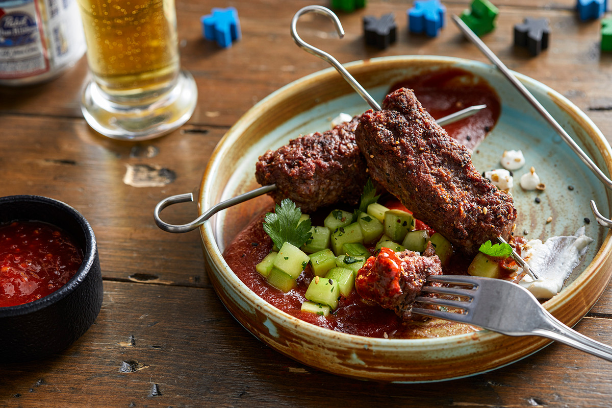 A dish with meat on skewers surrounded by beer and games.
