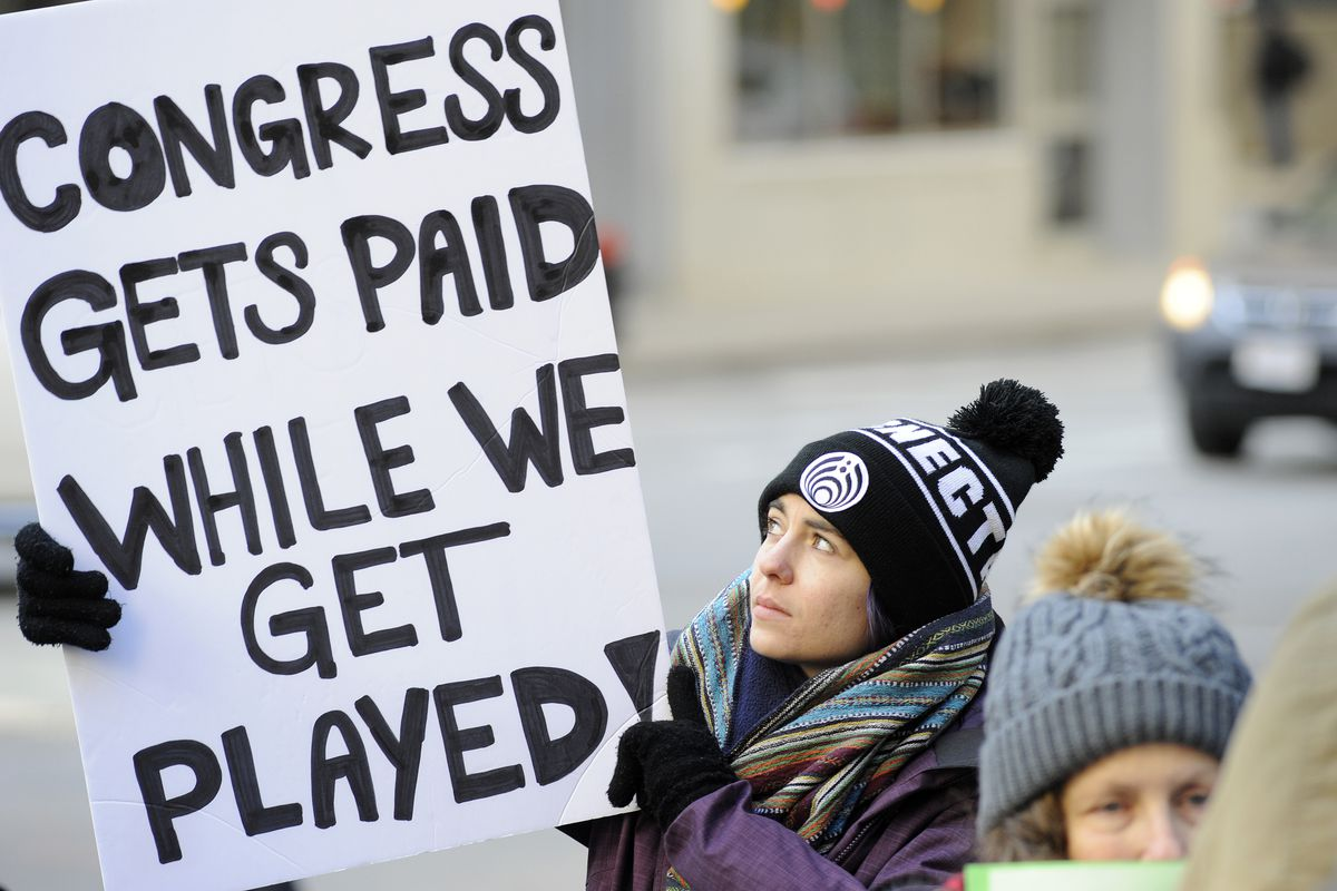 """A woman holds a sign reading """"Congress gets paid while we get played"""" in protest of the government shutdown."""