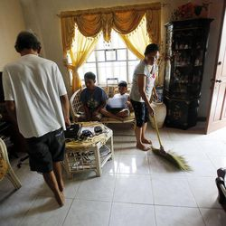 Ruby C. Rosales cleans house in Cebu, Saturday, Nov. 23, 2013. The Rosales family was displaced from Tacloban to the home of a friend following a typhoon.