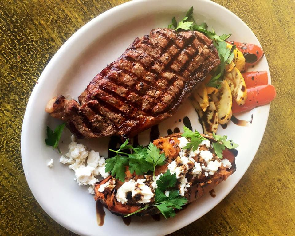 A plate of steak served with sweet potatoes topped with feta cheese and sliced squash and peppers