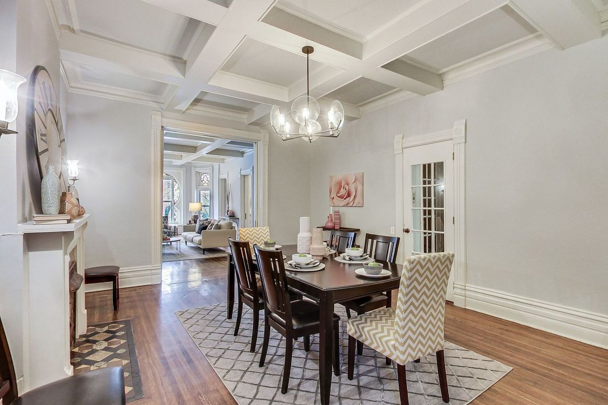 A large wood table sits in the middle of living room with coved ceilings and a fireplace. The table is surrounded by six chairs.