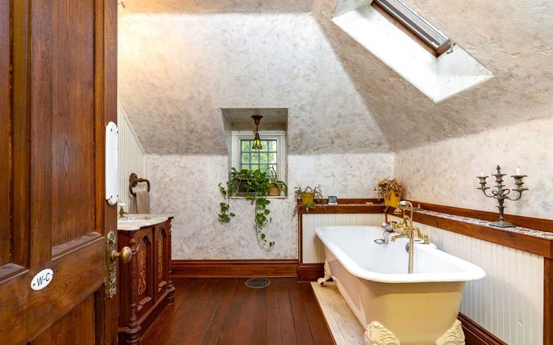 A master bathroom with yellow clawfoot tub, wood floors, and a skylight.