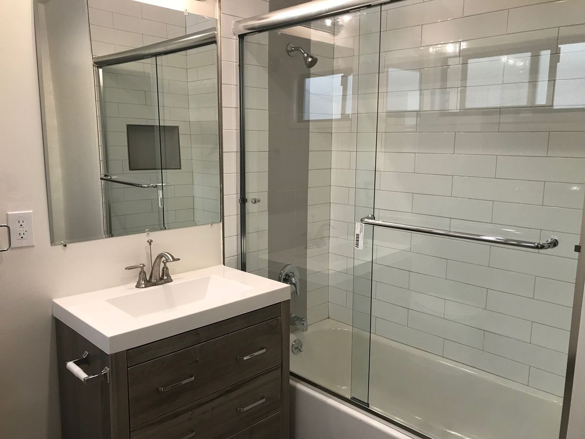 A bathroom with a small gray vanity and a shower with a glass sliding door