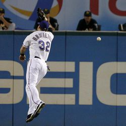 Texas Rangers center fielder Josh Hamilton (32) leaps but is unable to reach a triple by Oakland Athletics' Derek Norris in the first inning of a baseball game as the Athletics bullpen watches, Wednesday, Sept. 26, 2012, in Arlington, Texas.