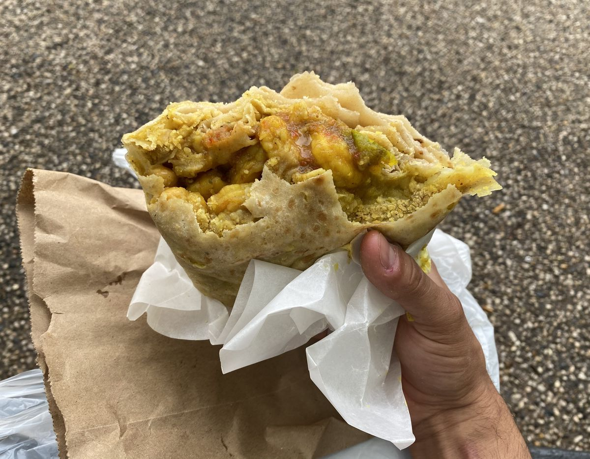 A hand holds a half-eaten roti filled with shrimp, chana masala, and hot sauce