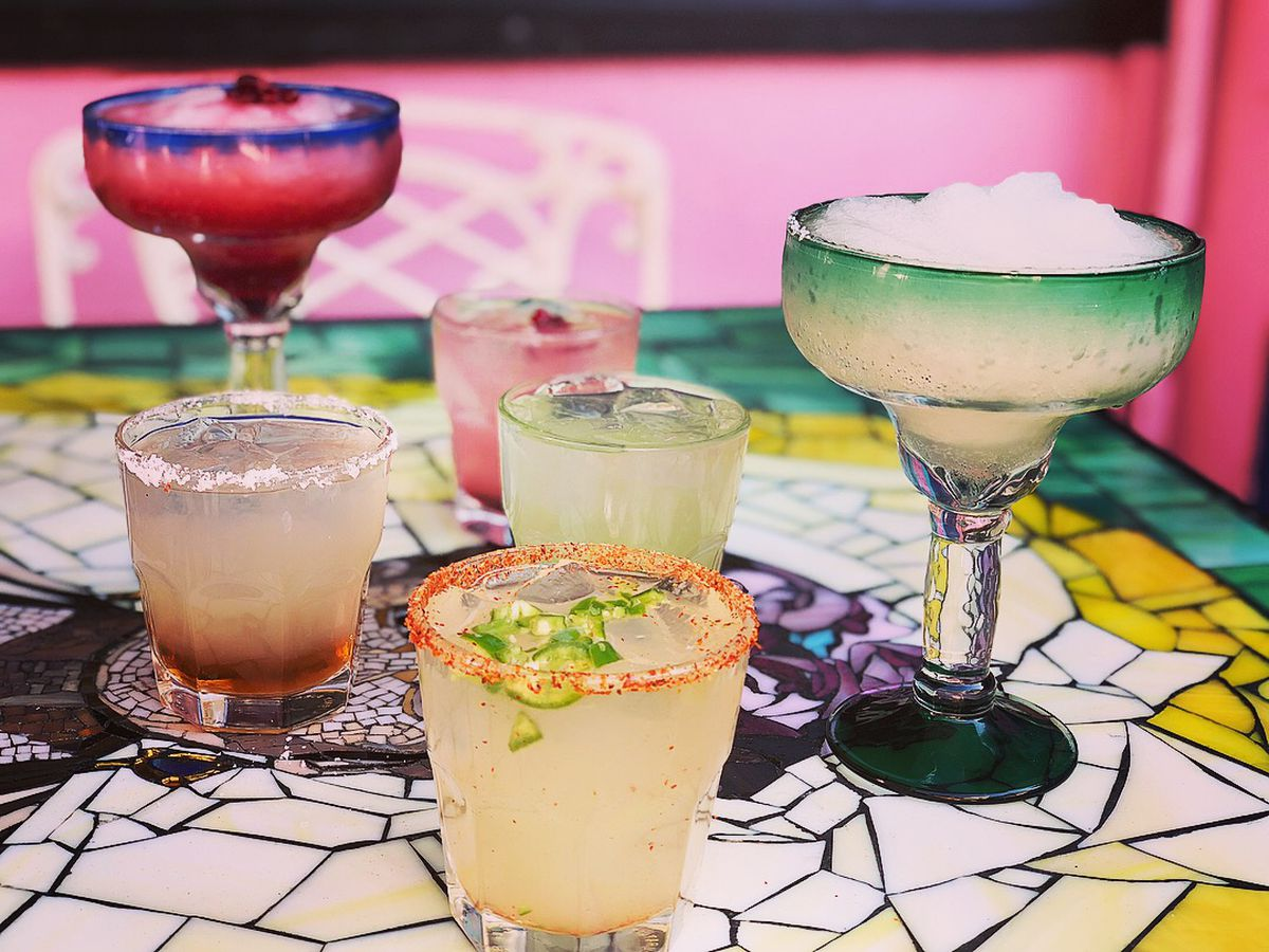 Margaritas and cocktails on a colorful restaurant table.