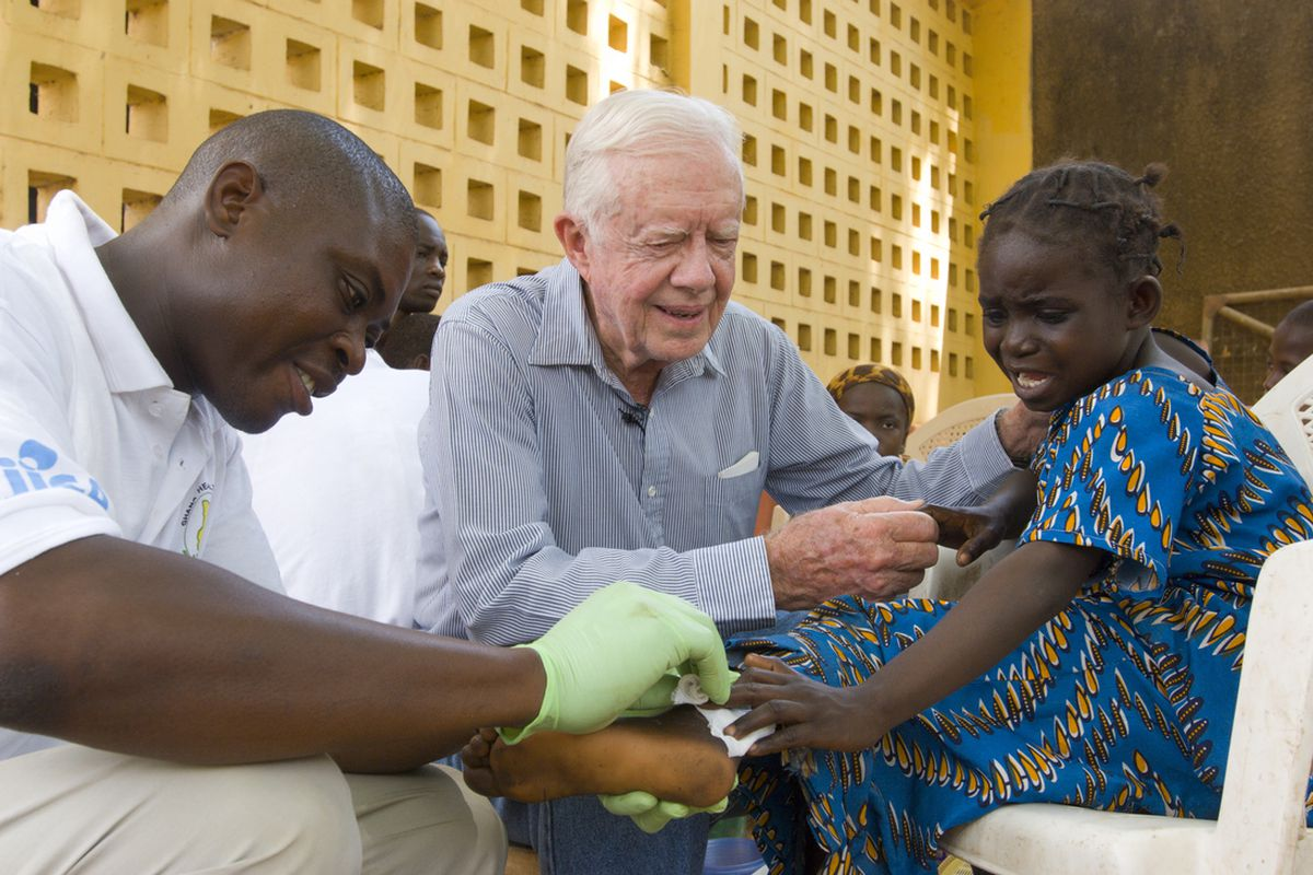 Former U.S. President Jimmy Carter tries to comfort 6-year-old Ruhama Issah at Savelugu (Ghana) Hospital as a Carter Center technical assistant dresses Issah's extremely painful Guinea worm wound on February 8, 2007.