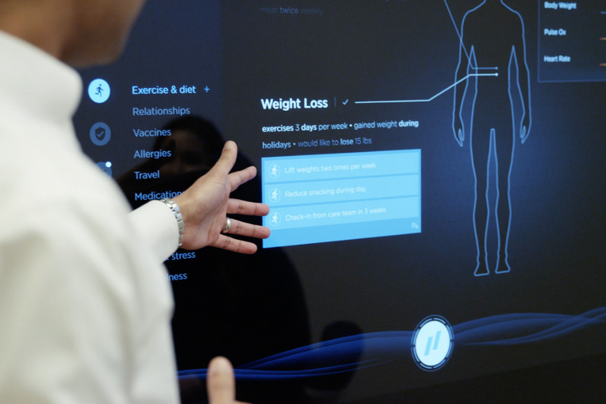 A primary care doctor at Forward looks over a patient's weight loss goals displayed on a screen.