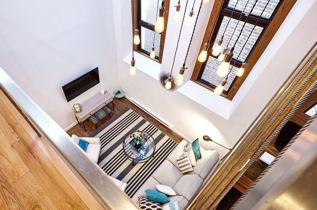 View from the very high living room ceiling, looking down on a square room with furniture and a TV.