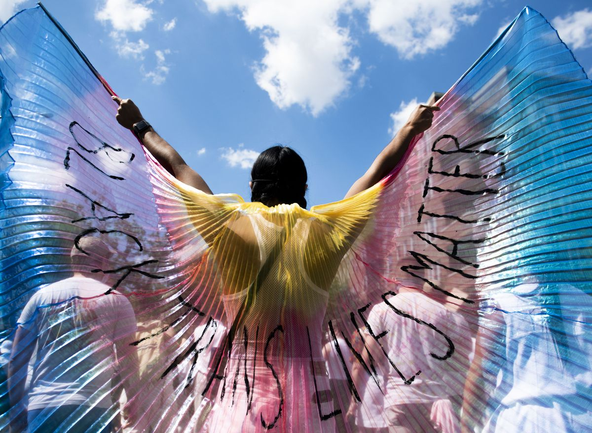 """Protester wearing large colorful wings that say """"Black trans lives matter"""""""