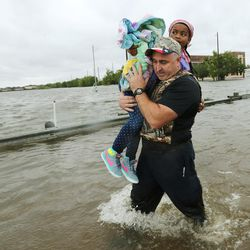 Deputy sheriff Trent Stegall carries evacuee Zoe Goree to dry land after she was rescued from floodwaters during Tropical Storm Harvey in Houston on Tuesday, Aug. 29, 2017. Stegall was working out of an LDS Church stake center boat command center.