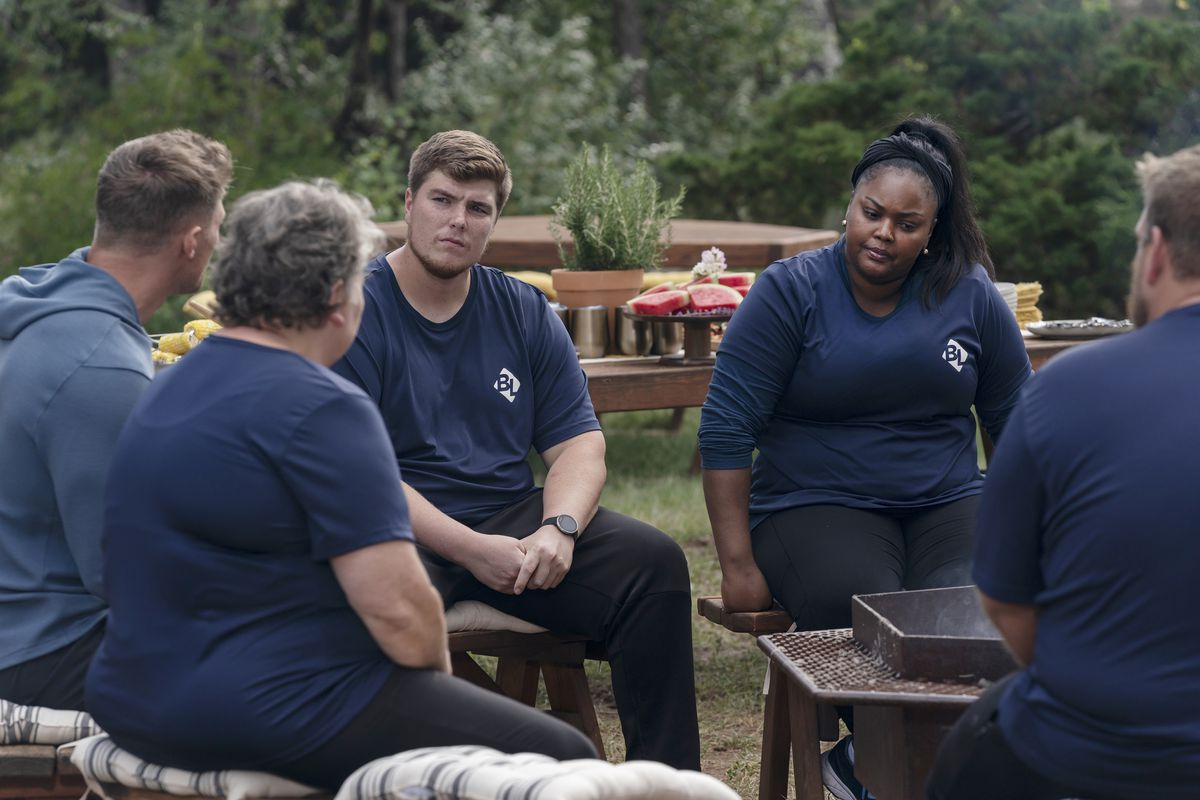 "Micah Collum (left) and Delores Tomorrow and the rest of the Blue Team meet with their team trainer/coach Steve Cook (far left) during an episode of ""The Biggest Loser."""