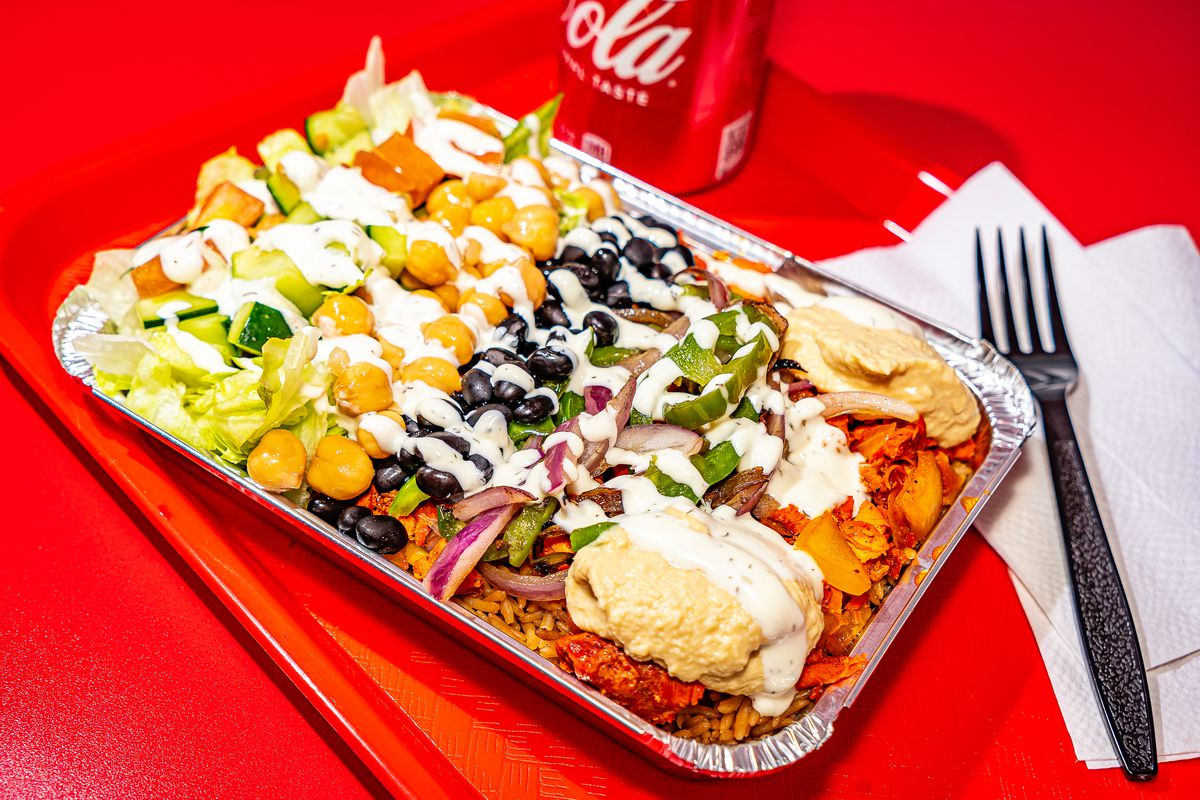 An aluminum container of chicken and rice, topped with white sauce, sits on a bright red tray on a bright red table. A plastic fork and can of Coca-Cola are visible in the background.