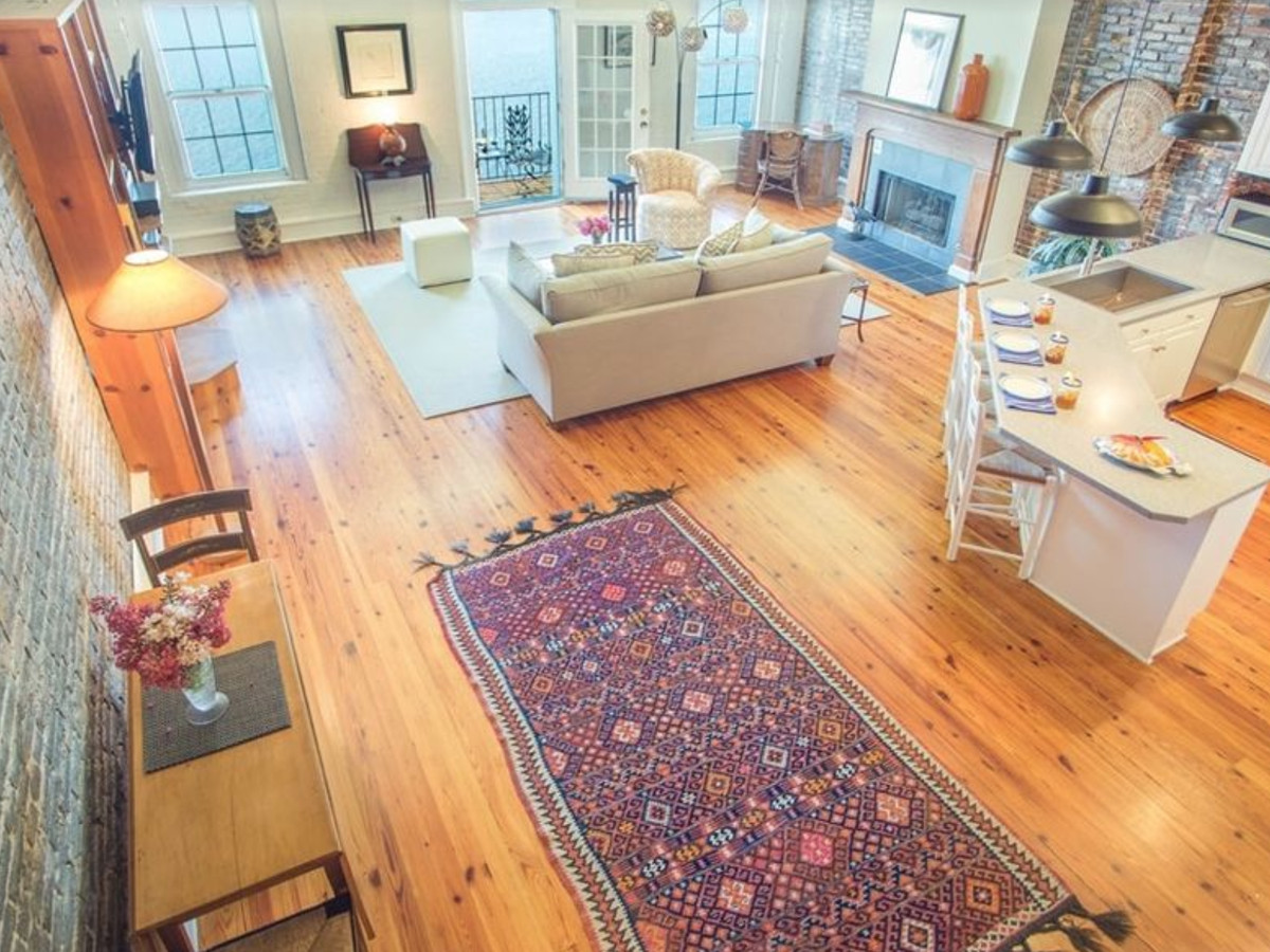 View of loft with living area and kitchen with area rug in the foreground.