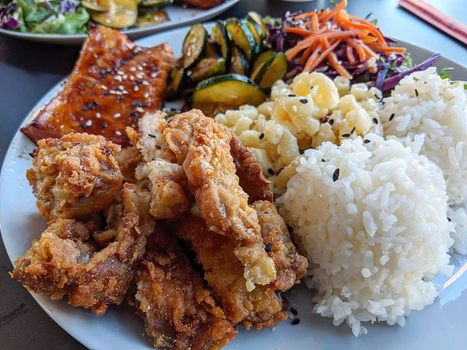 A plate of fried chicken, white rice, mac salad, kimchi, greens, and a chile-glazed piece of salmon belly