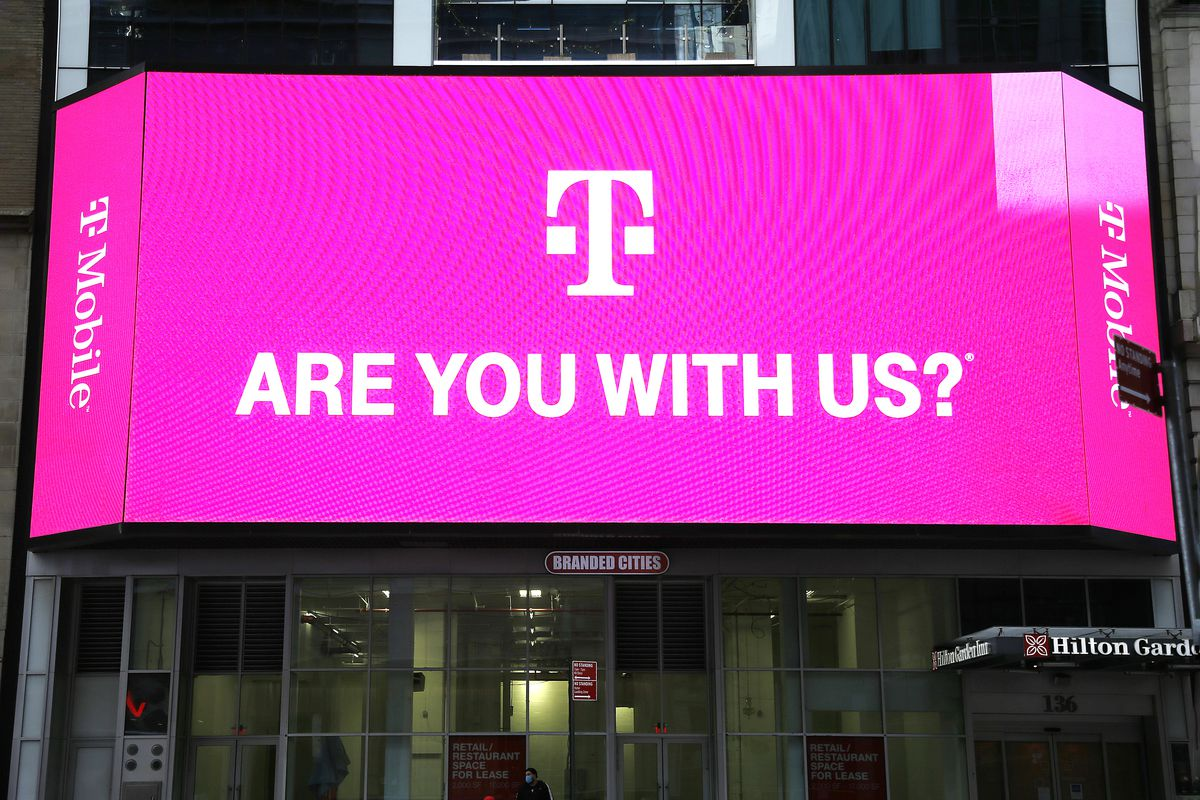 """T-Mobile network advertisement seen on a Jumbotron in Times Square reads, """"T-Mobile. Are you with us?"""""""