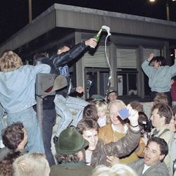 East and West Berliners mingle as they celebrate in front of a control station on East Berlin territory, Nov. 10, 1989, during the opening of the borders to the West following the announcement by the East German government that the border to the West would be open.