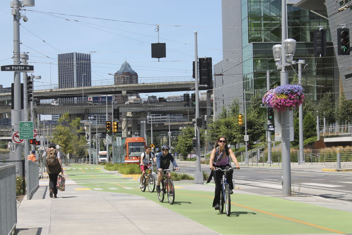 A city street with cyclists riding in bike lanes painted in green, pedestrians walking on a wide sidewalk, and a light rail line.