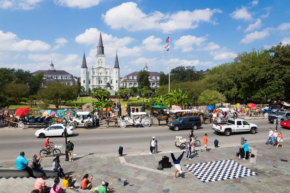 Jackson Square in New Orleans features a large white church in the background, with gardens in front of a busy street. Cars and horse-drawn carriages are in the street and street performers entertain tourists.