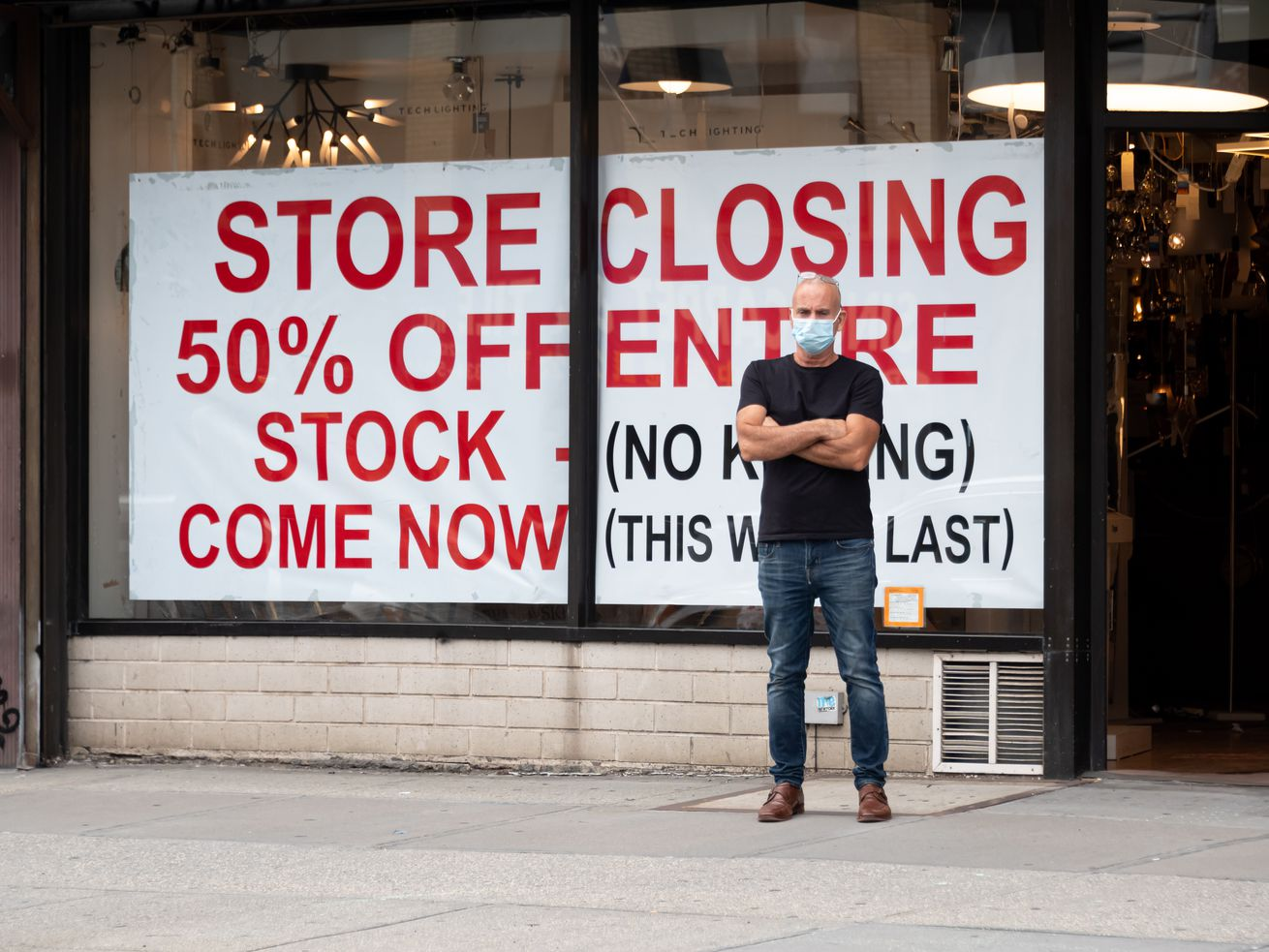 """A white man in a black t-shirt, blue jeans, and disposable mask stands with his arms folded in front of a store. A banner takes up 90 percent of the store's front windows. In bold red print, it reads: """"Store Closing 50% Off Entire Stock (No Kidding) Come Now (This Won't Last)."""