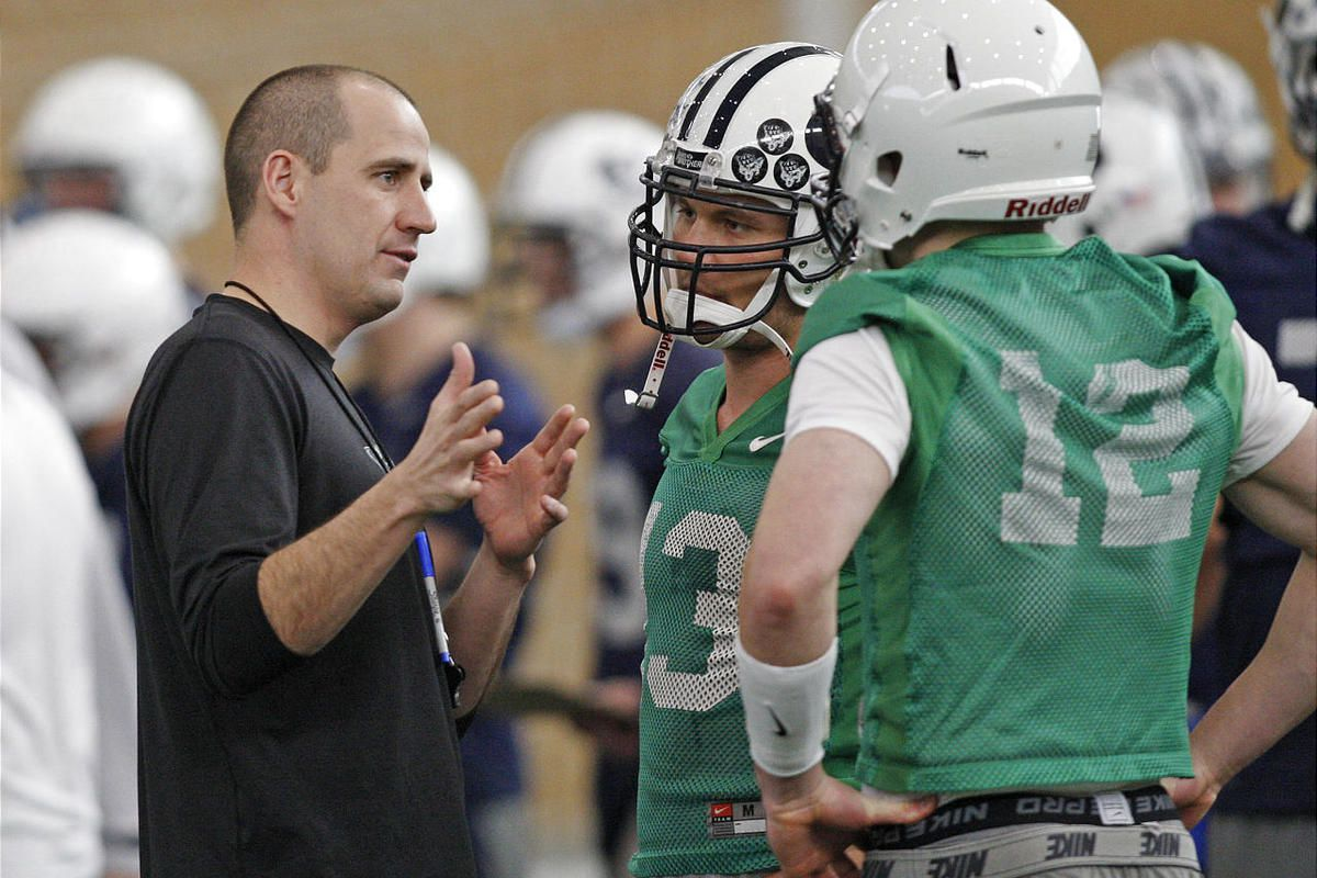 Assistant coach Brandon Doman talks with quarbacks Riley Nelson, center, and Taysom Hill on BYU's first day of spring football practice Monday, March 5, 2012, in Provo, Utah.