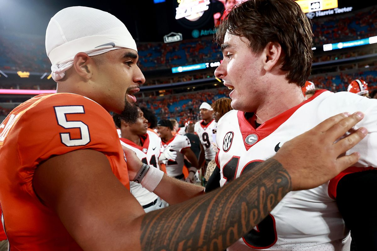 JT Daniels of the Georgia Bulldogs embraces D.J. Uiagalelei of the Clemson Tigers after the Duke's Mayo Classic at Bank of America Stadium on September 04, 2021 in Charlotte, North Carolina.