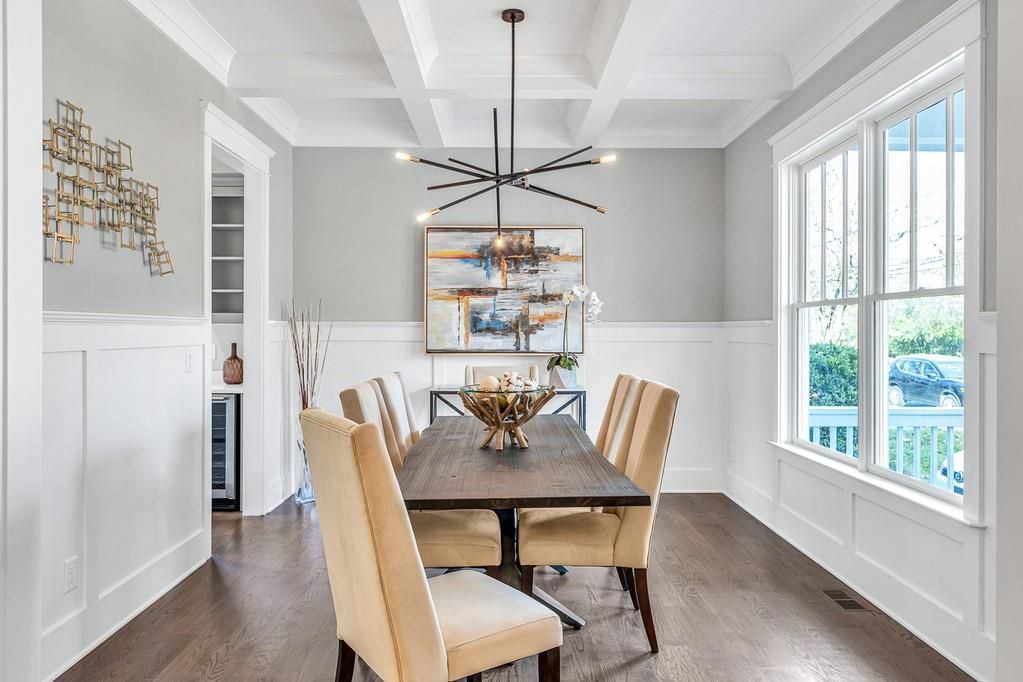 A dining room with a long wooden table and modern light fixture.