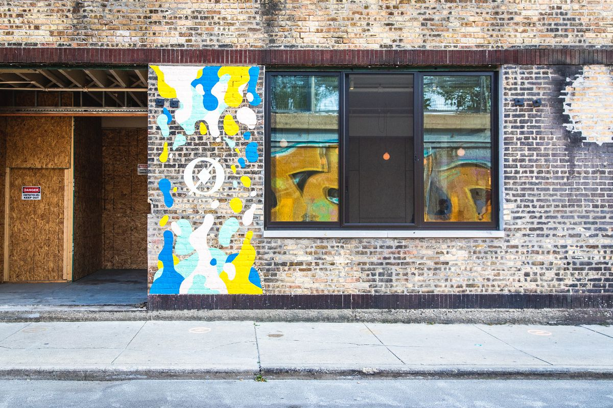 The exterior of a brick building with a mural of blue, yellow, white, and teal blobs.