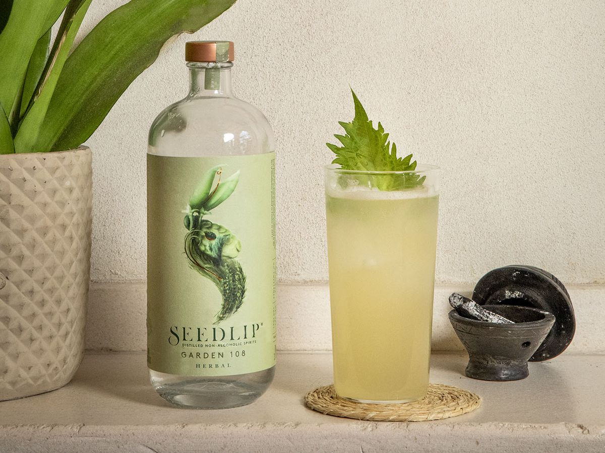 A fruity non-alcoholic cocktail with a green garnish sits on a coaster, at the Llama Son restaurant. A bottle of Seedlip, a non-alchoholic spirit, sits to its left.