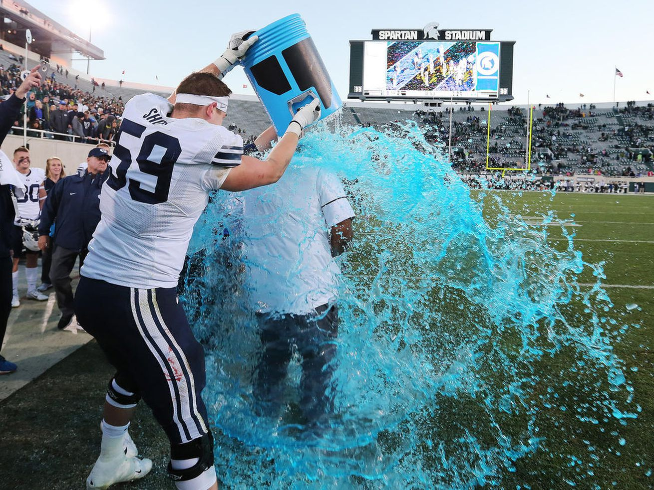 BYU head coach Kalani Sitake gets doused by Cougars offensive lineman Thomas Shoaf (59) during the BYU-Michigan State game in East Lansing, Mich., on Saturday, Oct. 8, 2016. BYU won 31-14.