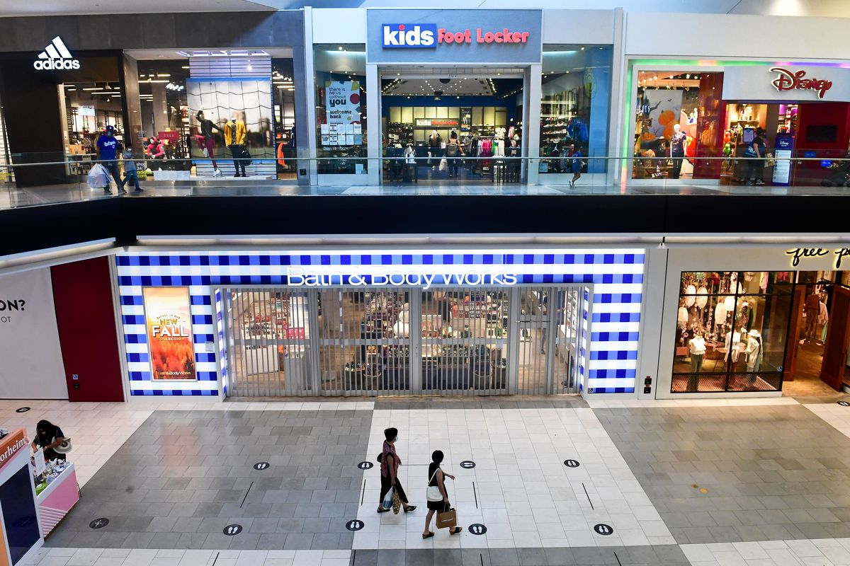 Interior of a mall, showing two stories of stores.