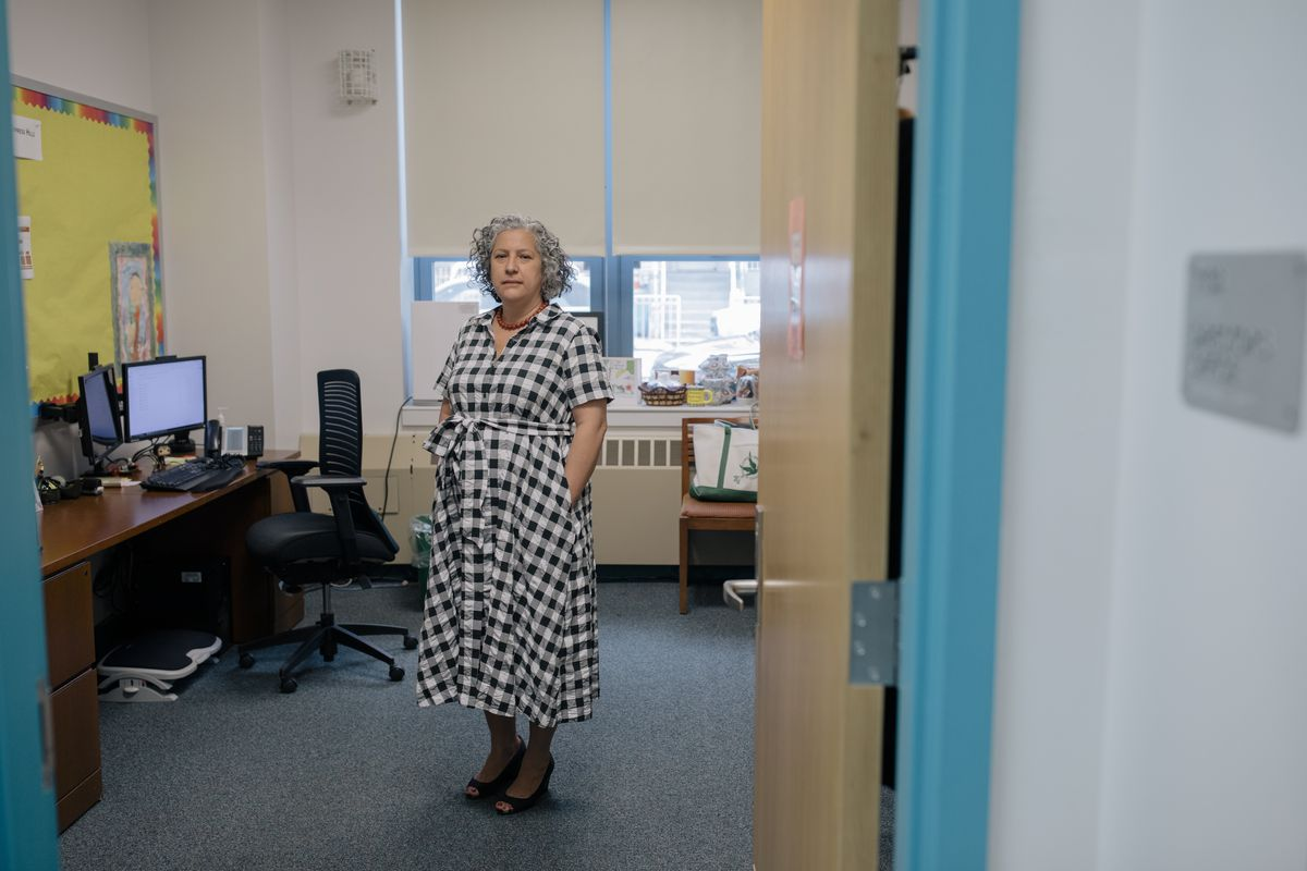 Principal Irene Leon, wearing a black and white checkered dress, stands in her office while the blue doorframe of her entrance sits in the foreground.