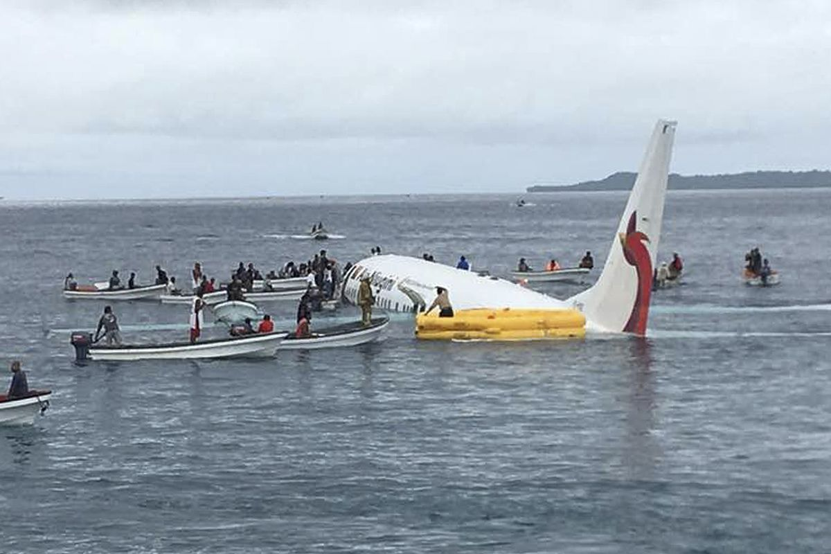 FILE - In this Sept. 28, 2018, file photo, local fishing boats move in to recover the passengers and crew of Air Niugini flight following the plane crashing into the sea on its approach to Chuuk International Airport in the Federated States of Micronesia.