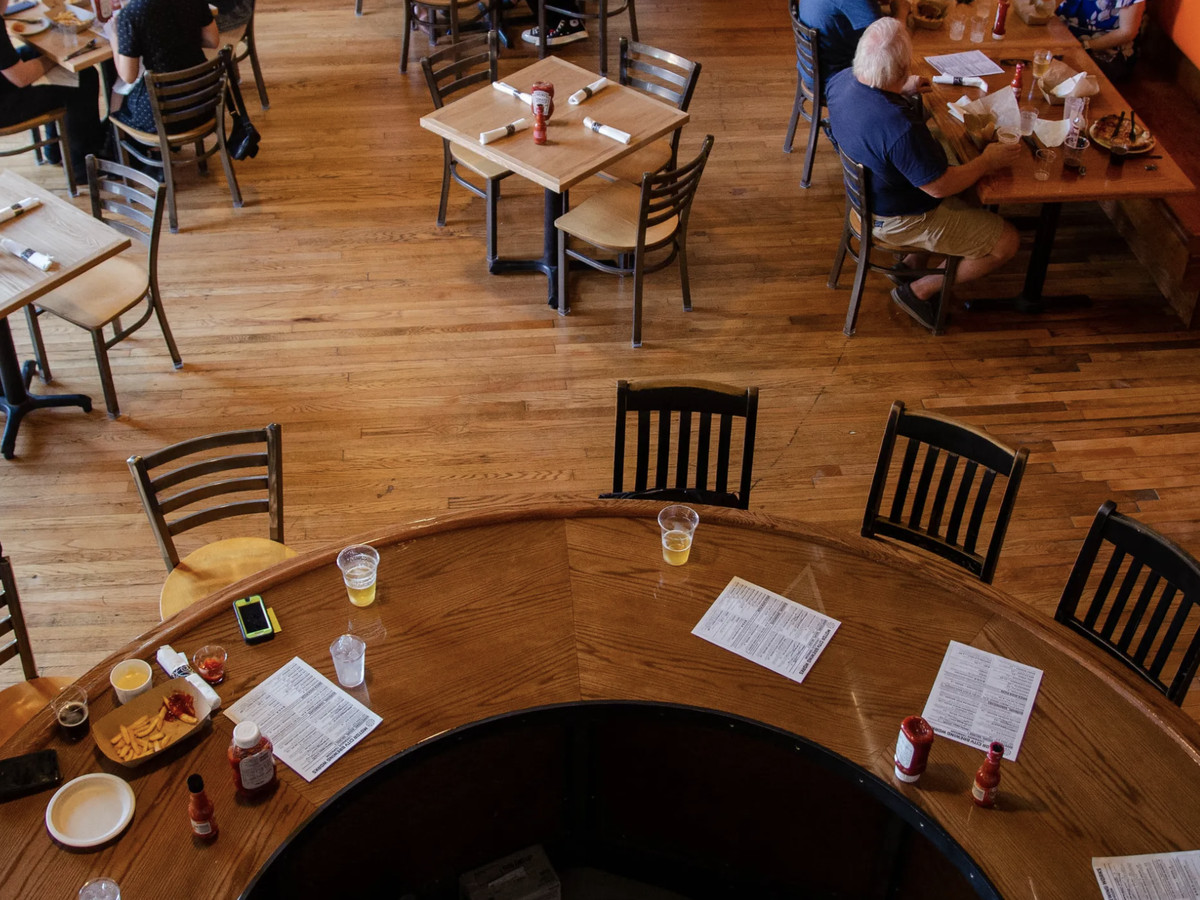An aerial view of the dining room at Motor City Brewing shows dining room with patrons sitting at tables. The hardwood floors have been sanded and polished to a shine.