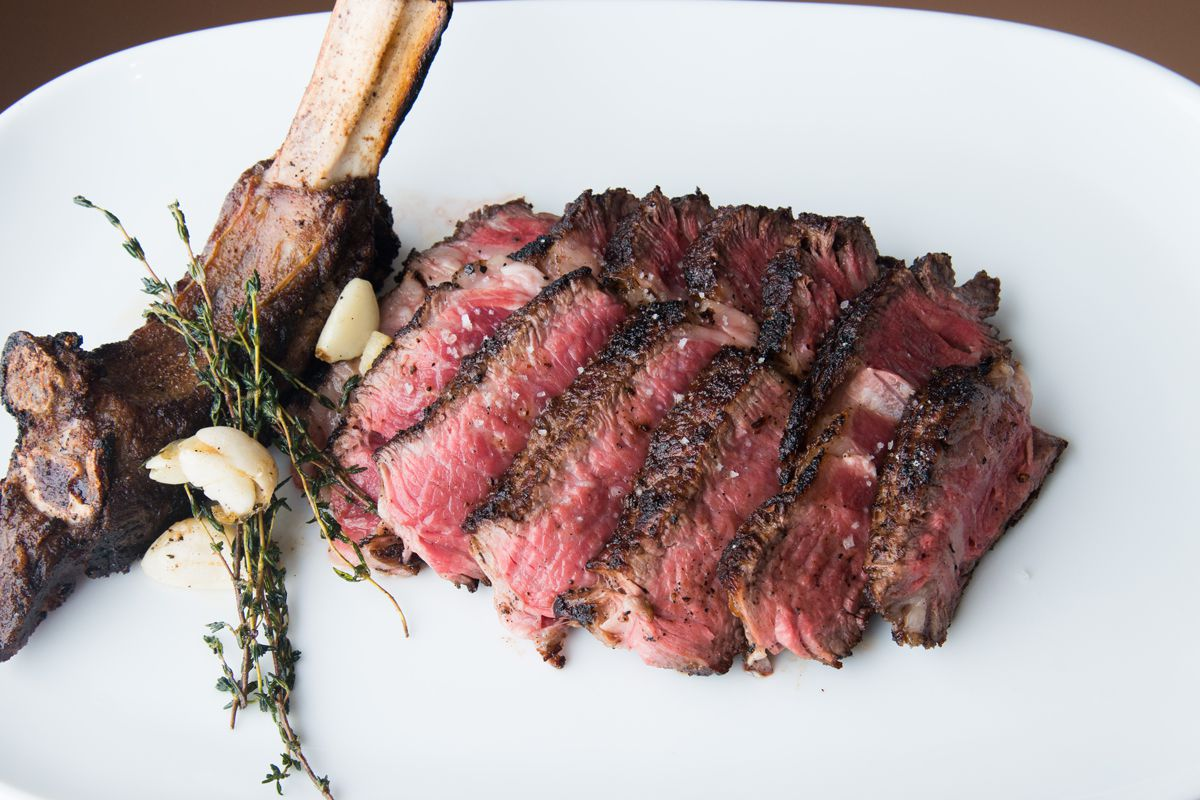 A steak cooked medium rare and sliced off the bone, with the bone to the left side, presented on a white plate, at Cut, one of London's best steak restaurants
