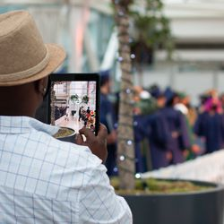 A man records Simon Youth Academy graduates on an iPad as they leave the Indianapolis Artsgarden at the conclusion of their graduation ceremony Thursday.