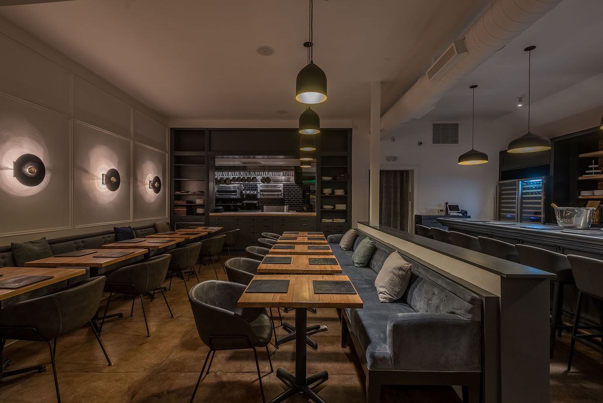 Dimly lit interior with tables and hanging lights at Kass restaurant in Los Angeles
