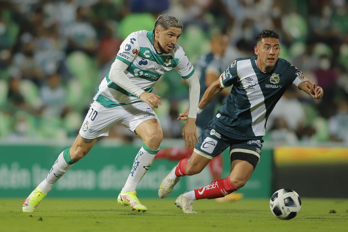Diego Valdes of Santos (L) fights for the ball with Daniel Alvarez of Puebla during the 9th round match between Santos Laguna and Puebla as part of the Torneo Grita Mexico A21 Liga MX at Corona Stadium on September 19, 2021 in Torreon, Mexico.