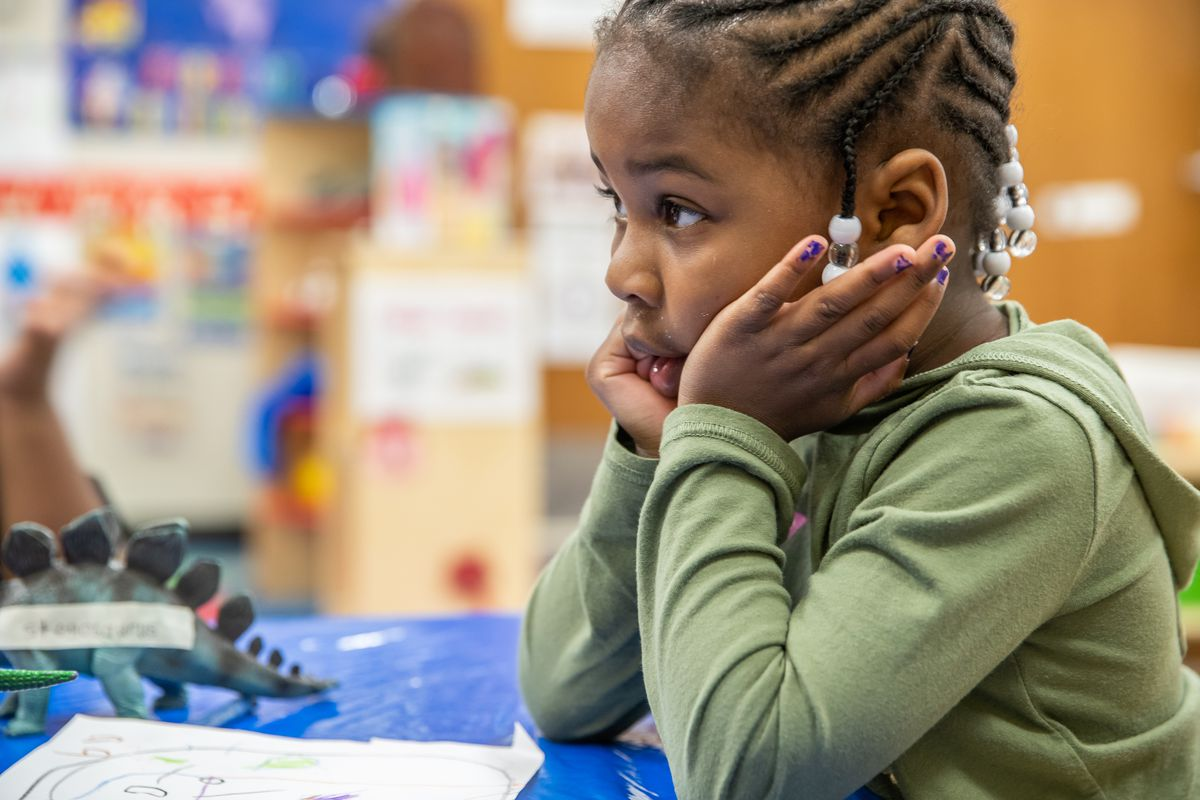 Prius Winters, 4, a pre-kindergarten student at Avondale Meadows YMCA Early Learning Center in Indianapolis, waits for teacher, Cecelia Washington, to label her drawing of her favorite dinosaur during a lesson on Tuesday, April 30, 2019.
