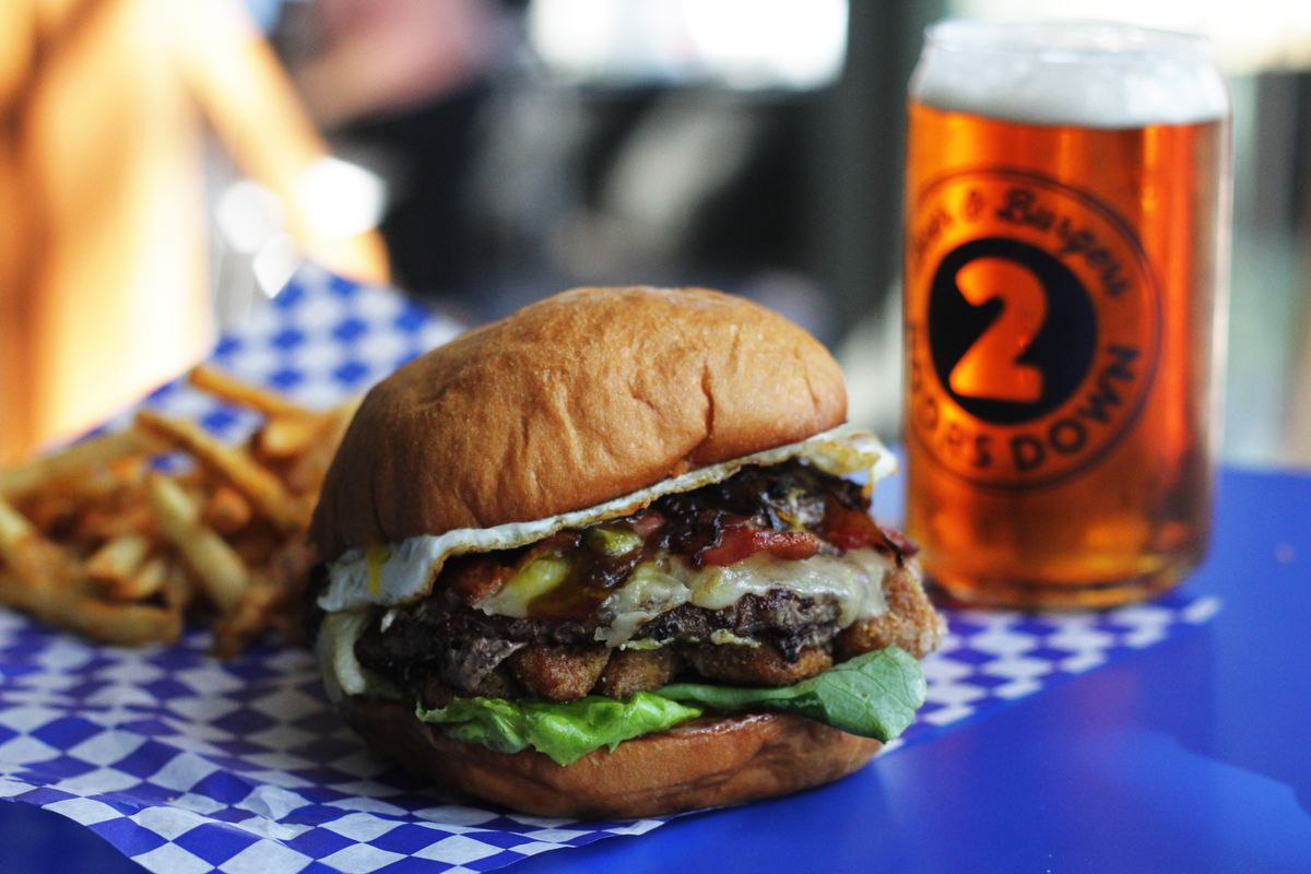 A burger loaded with toppings at Two Doors Down, next to a full glass of beer and fries in the background