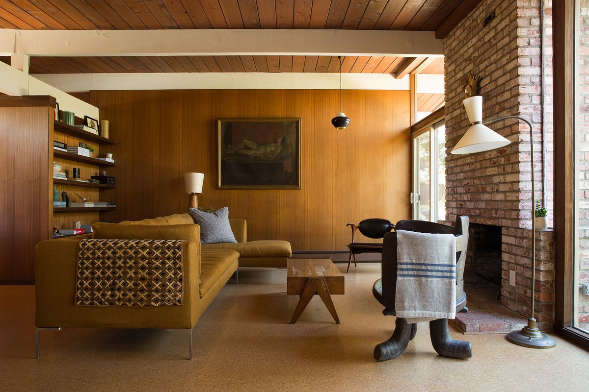 Living room with wood-paneled walls, tongue-and-groove beamed ceilings, brick fireplace, cork flooring, built-in shelving, and furnished with a sectional sofa, wood coffee table, lamp, and sculptural chair.