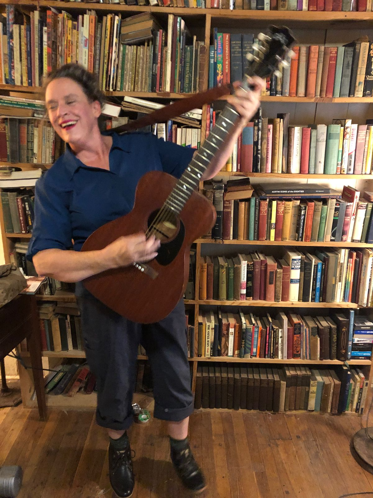 A white 50-something woman holding up an acoustic guitar as she plays, looking to the side and laughing. There is a floor-to-ceiling bookshelf full of books behind her.