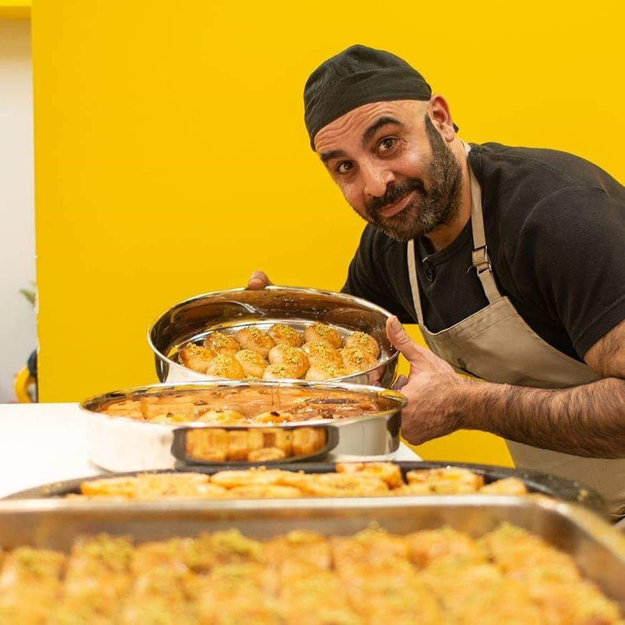 A chef in a skullcap and apron holds up a tin of baklava on a table with other pastries in front of a bright yellow wall