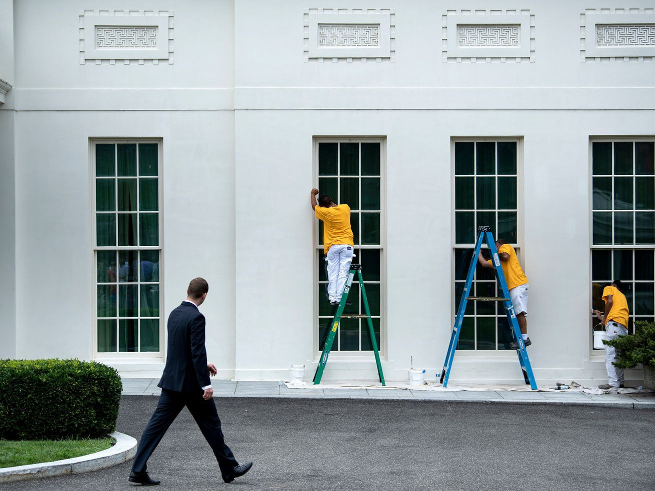 Three men in yellow shirts touch up the paint around the windows on the first floor of the White House.