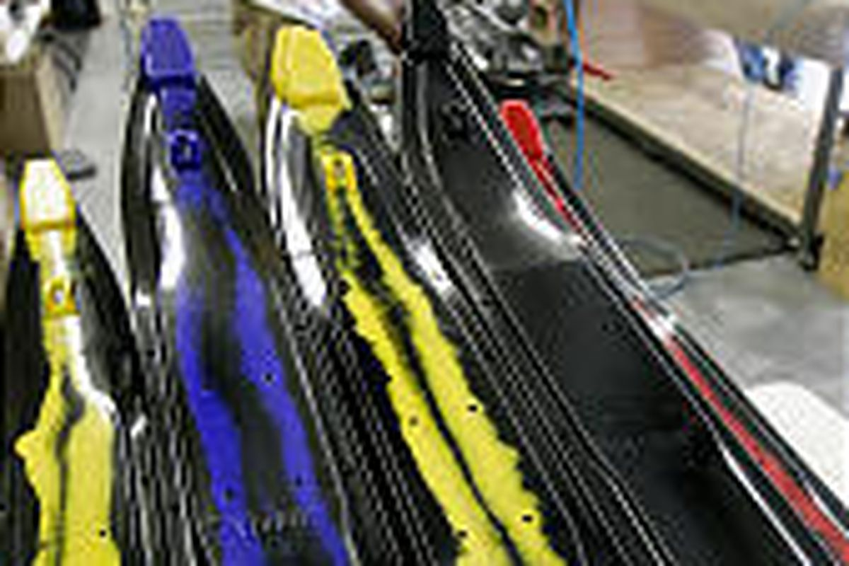 Michael Olsen, left, talks with grandfather Verlin Simmons while assembling snowmobile skis Simmons invented. Bombardier Inc. has been selling copycat version.
