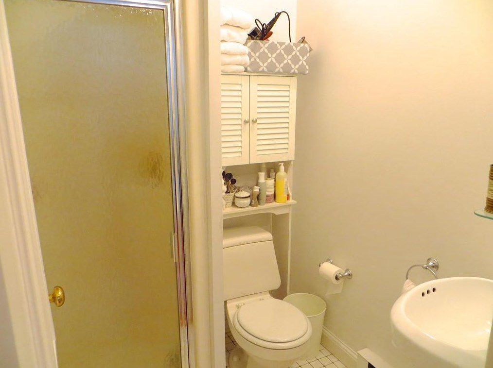 A small bathroom with the toilet in a corner next to the slender shower with a plastic door.