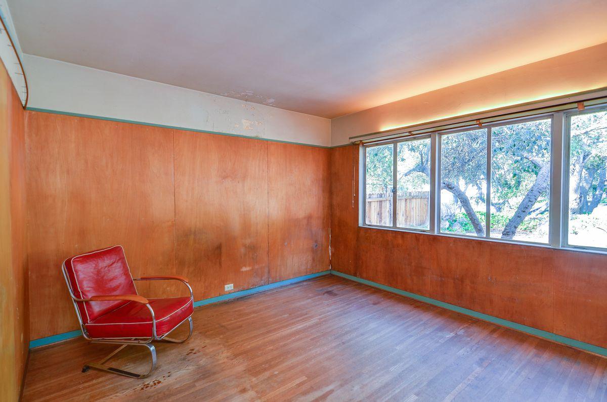 Bedroom with wood paneled walls