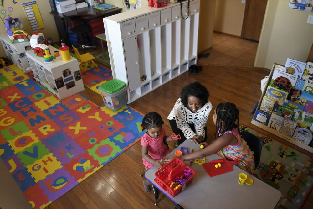 Yemi Habte cleans up for snack time with her daughters, Anna Mandefro 2, and Charis Mandefro, 9, during a session with Stephanie Olson, a MyVillage mentor in her home. (Photo by Joe Amon/The Denver Post)