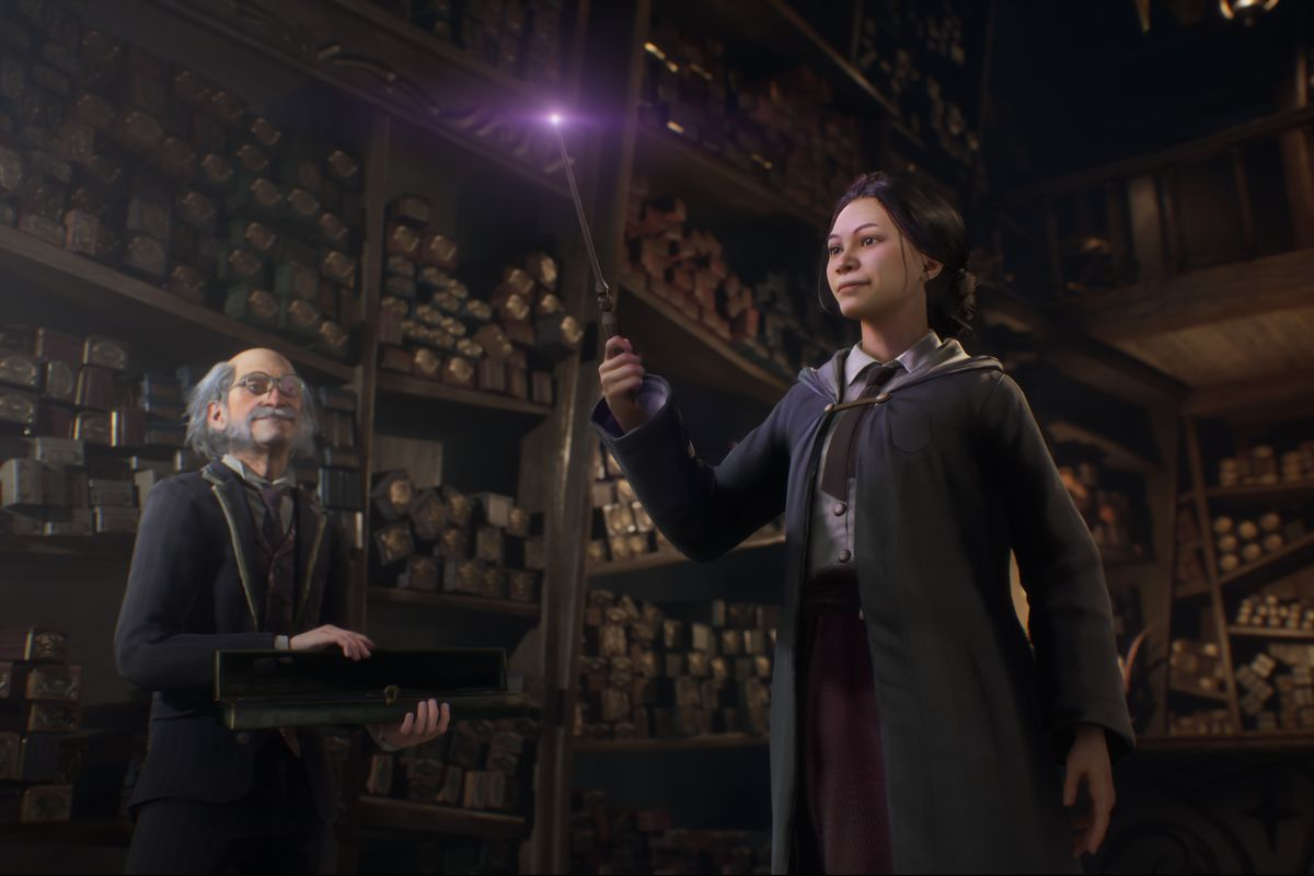 a Hogwarts student holds a wand in a wand shop as an elderly man looks on in Hogwarts Legacy